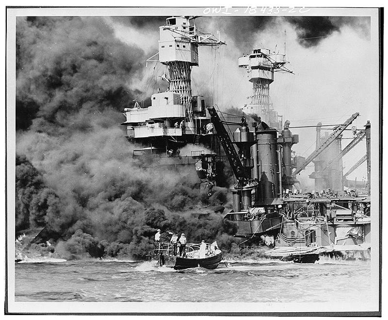 Pearl Harbor, Hawaii, Dec. 7, 1941. A small boat rescues a seaman from the 31,800 ton USS West Virginia burning in the foreground. Smoke rolling out amidships shows where the most extensive damage occurred. Note the two men in the superstructure.