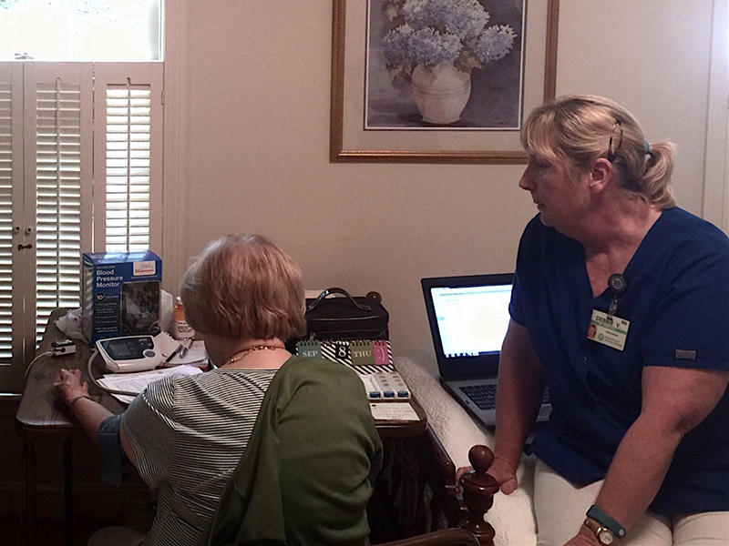 Home health nurse watching over patient as she sends vitals in to be analyzed.