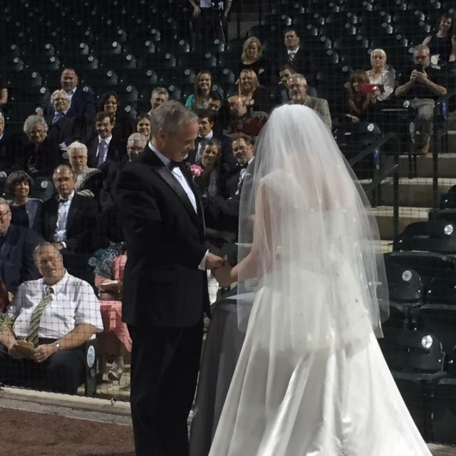 Mr. and Mrs. Mark Cain sign their wedding certificate before friends at the Columbia Fireflies ball park.