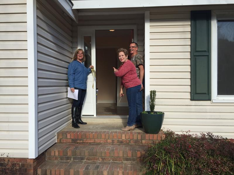 Irmo Resident Karen Elliot cuts a ribbon to welcome neighbors, rebuild volunteers and friends into her repaired home.