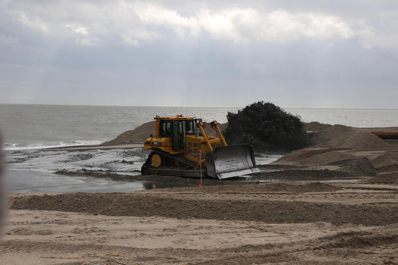 Bulldozer moves sand pumped from offshore onto Edisto Beach to extend beach and protect against hurricanes.