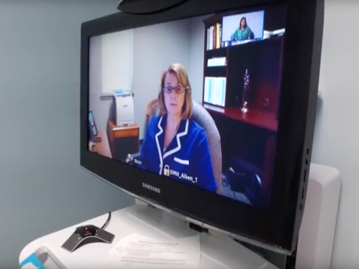 Sitting in her office, in Aiken, S.C., Dr. Ratliff conducts a telepsychiatry consultation to a patient sitting in a private room located at one of the emergency departments in S.C.