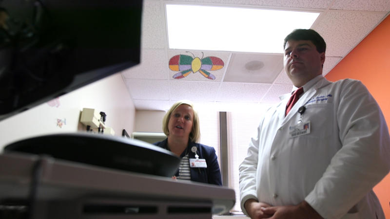 Pediatric burn physicians consulting remotely with patient through telemedicine cart.