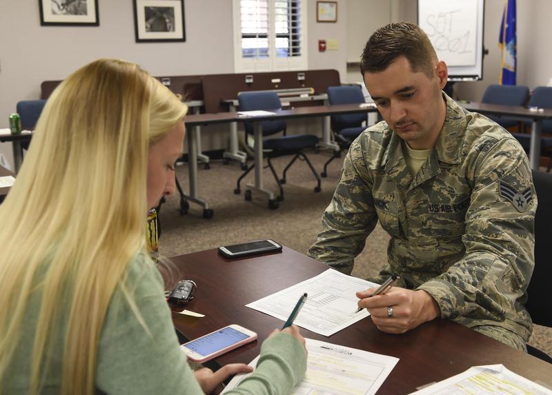 Megan Doty (left), 628th Security Forces Squadron unit program coordinator, files out her travel voucher with Senior Airman James Hauck, 628th Comptroller Squadron financial technician.