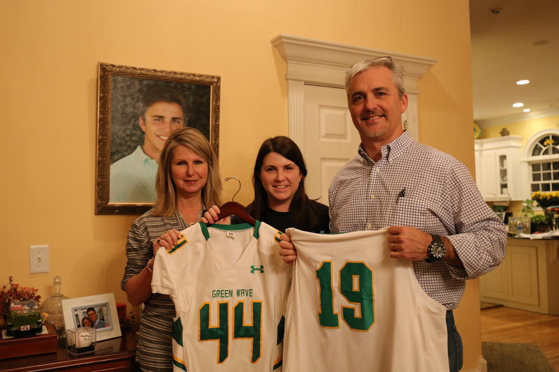 In front of Tripp's photo his mother Sandra, sister Emily and father Glenn Rabon hold his baseball and football jersey. Tripp was killed in a car crash in December 2015.
