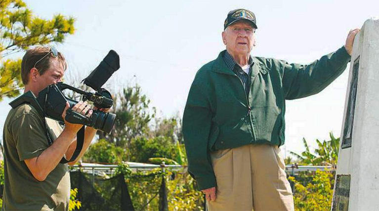Retired Col. Ted Bell, his son, Ted Bell, Jr. and a film crew visited Okinawa, Japan, to revisit the site of a battle Bell lead during World War II. Here, filmmaker Wade Sellers films Bell at a memorial for Ernie Pyle at Peace Memorial.