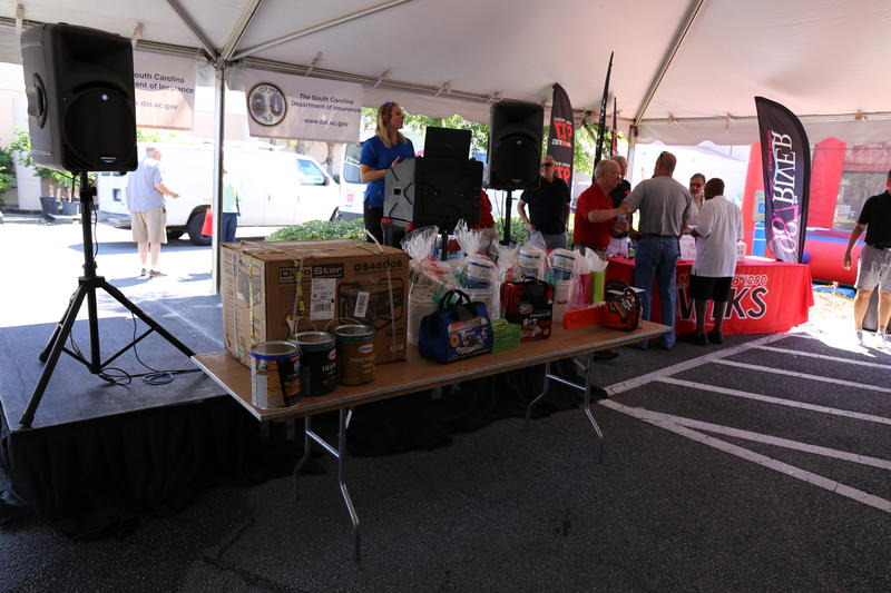 A photo of a table in front of the event stage, covered with door prizes for attendees, all items useful for emergency weather preparedness.
