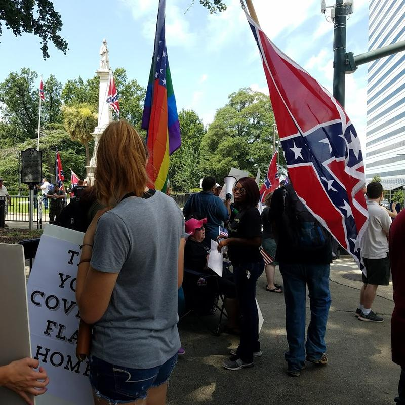 Confederate flag supporters walk through a group of protestors in front the South Carolina Statehouse.