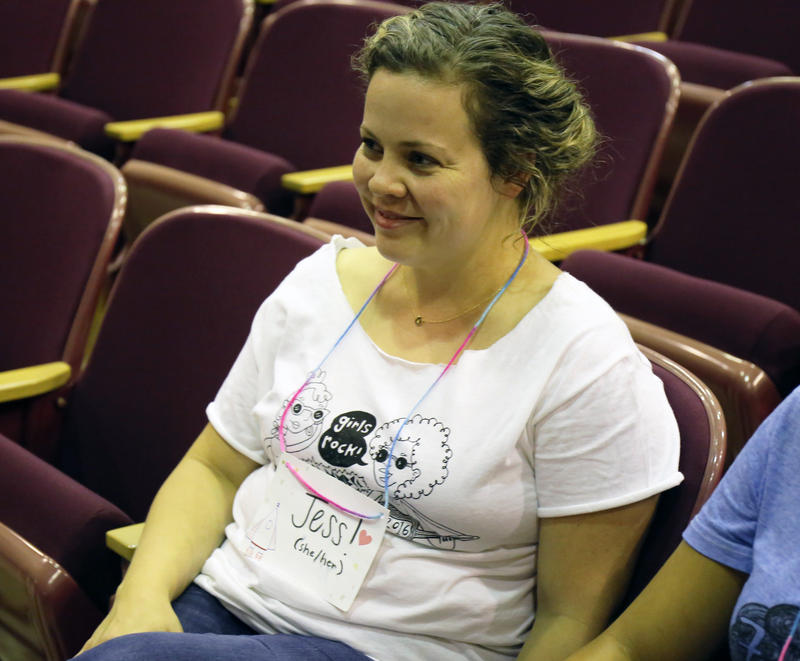 The incoming Executive Director, Jess Oliver, watches a group of girls rehearse in the auditorium.