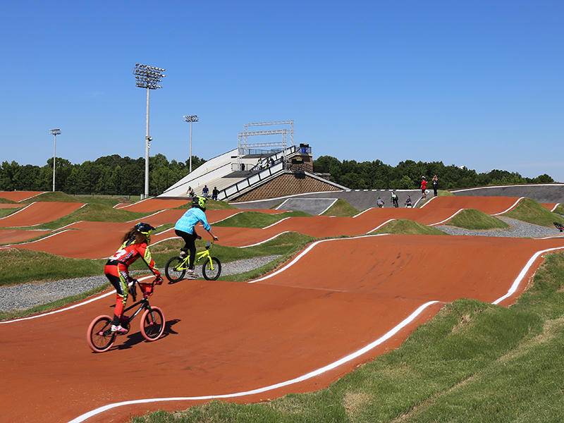 A rolling course is rehearsed by a media member and coach, heading for the finish line at the Rock Hill BMX track.