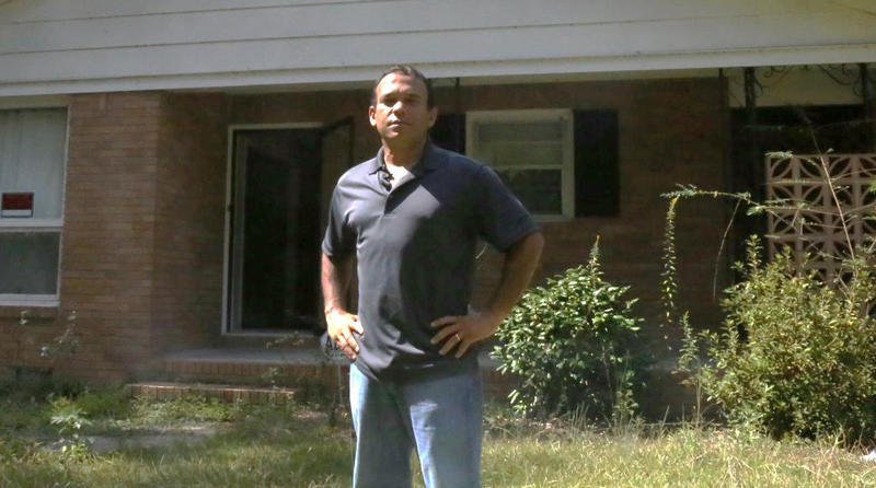 Retired Army Major Miguel Santana stands in front of his home in Columbia. Santana says he is a victim of contractor fraud and it's stalling his flood recovery.