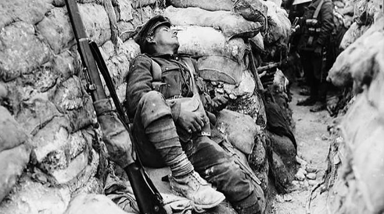Soldier's comrades watching him as he sleeps, Thievpal, France, during World War I.