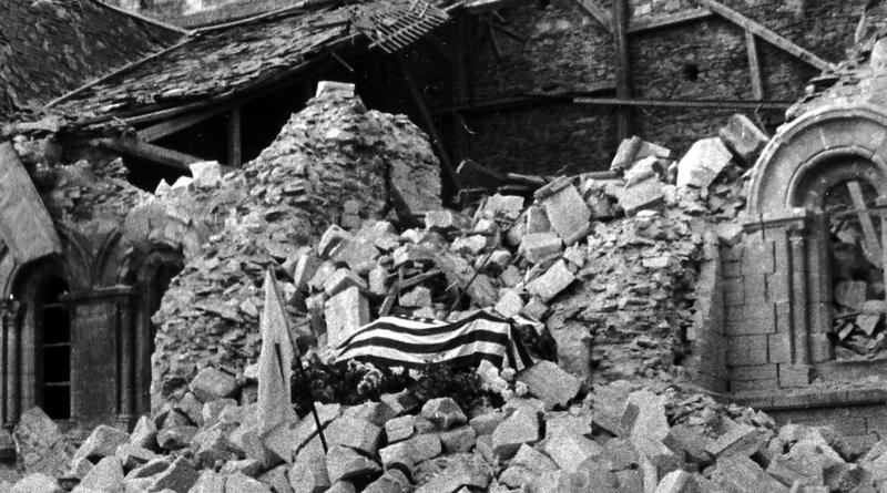 The flag-draped body of Maj. Thomas Howie rests on the rubble of the St. Lo Cathedral, 1944.