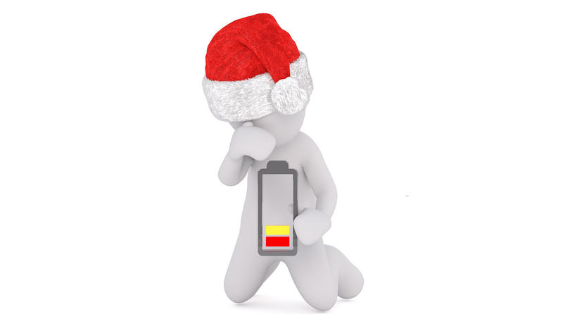 "illustration of a male figure in a Santa who is holding a battery that is ""low"" on power"