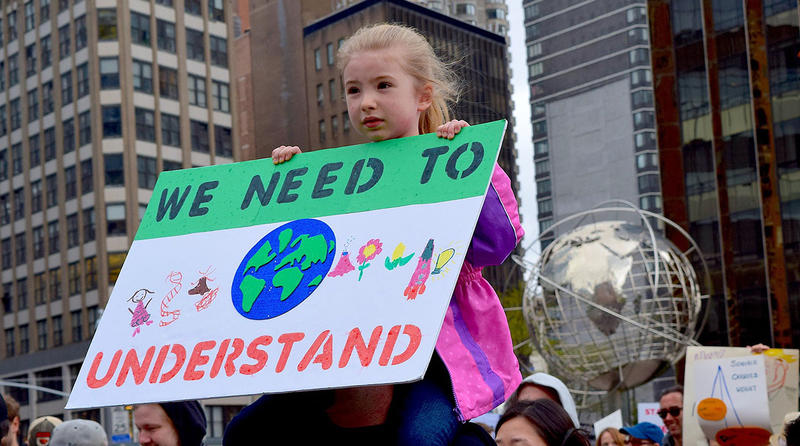 A little girl holding sign at a march. The sign depicts the earth and is captioned,