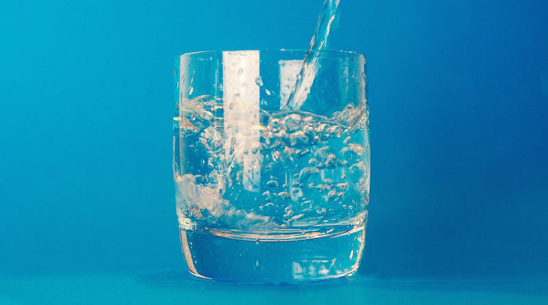 file photo of water pouring into a drinking glass