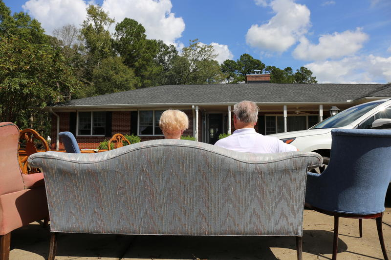 Bill and Diane Parker sit outside their flood ravaged home in Conway.