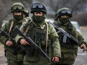 Armed men, believed to be Russian servicemen, march outside an Ukrainian military base in the village of Perevalnoye near the Crimean city of Simferopol March 9, 2014.