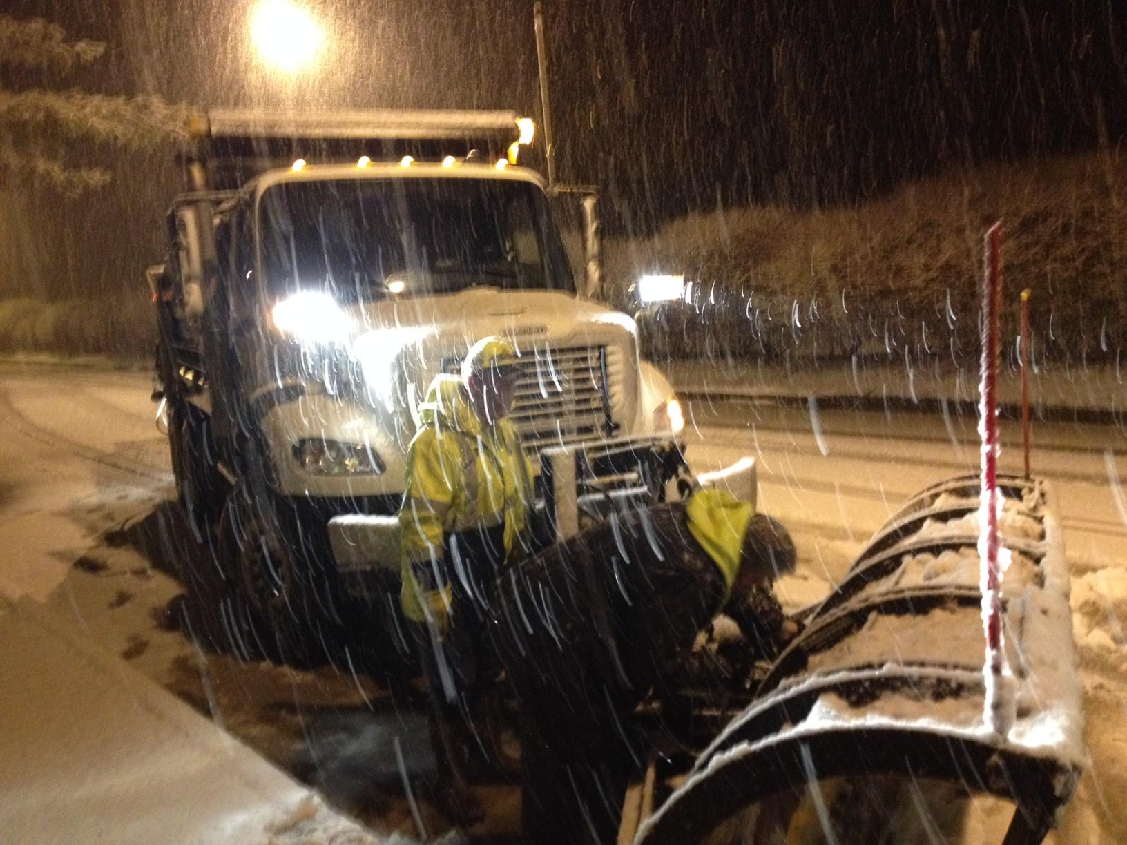 Kentucky Department of Highways crewmen on the road in Rowan County Wednesday night during the snow, pulled over as a mechanic works on a plow blade.