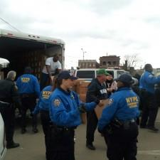 Officers with the New York Police Department help unload a shipment of emergency food supplies sent to the East Coast by the Nashville based ministry Church of Christ Disaster Relief