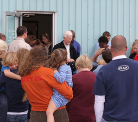The homeless and volunteers gather for prayer outside the offices of the Murfreesboro charity The Journey Home before sharing a meal.