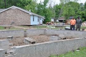 Mid-state residents examine a home pushed off its foundation by the 2010 floods.
