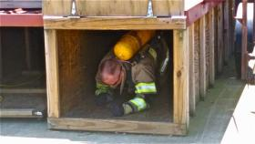 MFD Firefighter Paul Oliver crawls through a box during his annual firefighter skills test to prove that he can negotiate tight spaces while wearing a full set of personal safety equipment.