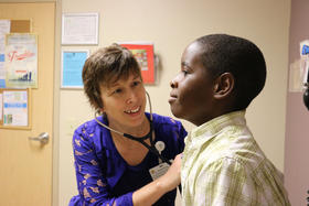Dr. Amy Vehec checks Matt Morehouse's breathing during his appointment.