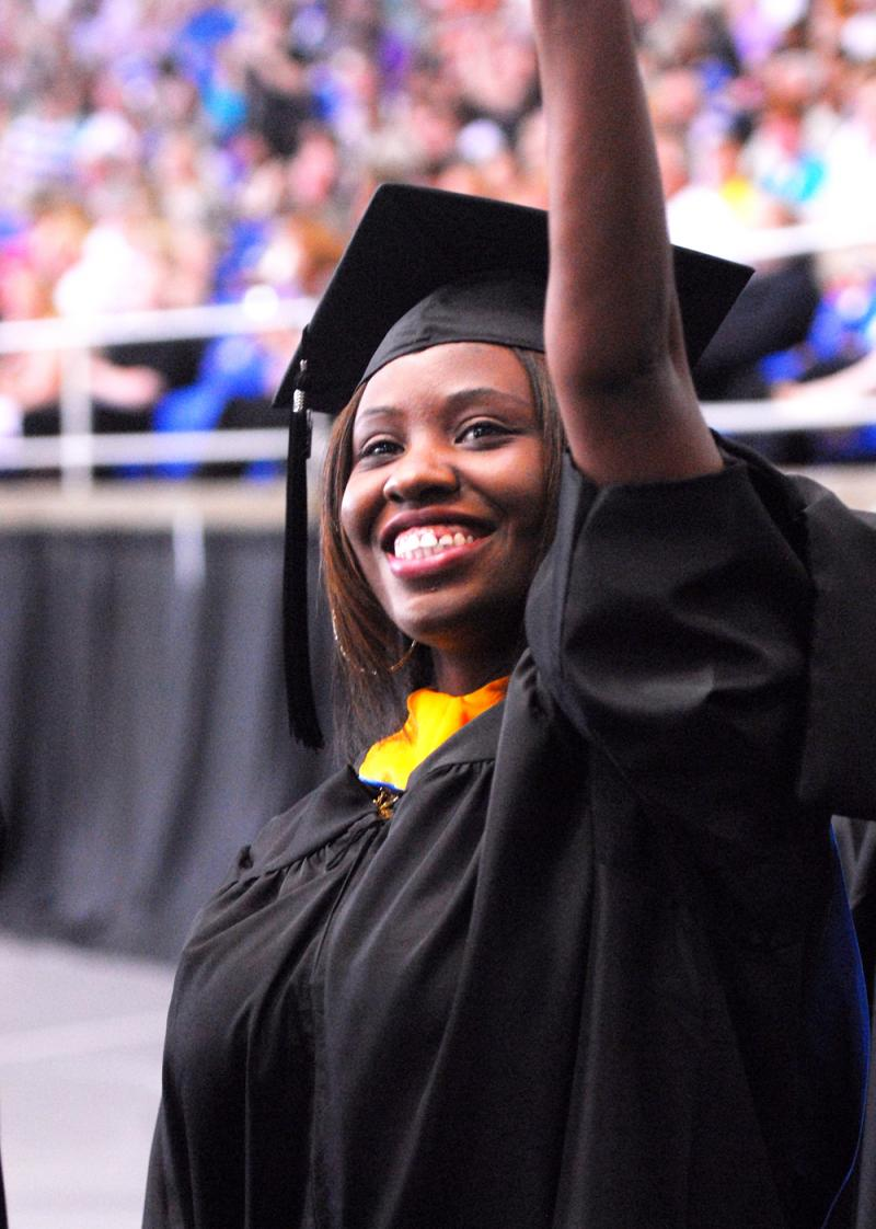 An MTSU degree candidate waves to her friends and family as she enters Hale Arena at Murphy Center for the spring 2012 commencement ceremonies May 5.