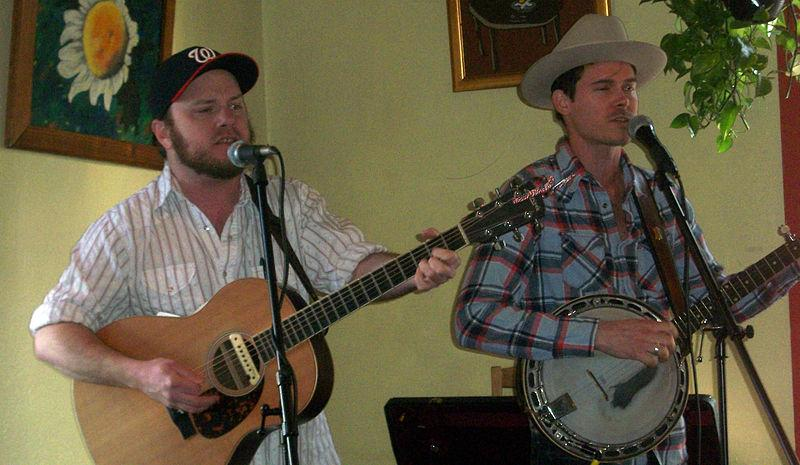 "Crows ""Critter"" Fuqua (guitar) and Ketch Secor (banjo) play at Little Grill Collective in Harrisonburg, Virginia (at 2012's Our Community Place benefit). Photo credit: Wikipedia user Michael J. Farrand via Wikipedia Commons."