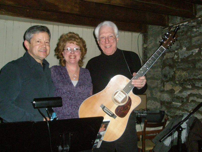 Doug Arthur (right, holding guitar) with fellow trio members. Photo credit: TheRhondaSagerTrio.com