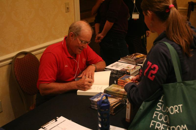 Joel Salatin signs one of his books at the Food Freedom Festival in Staunton, Va.