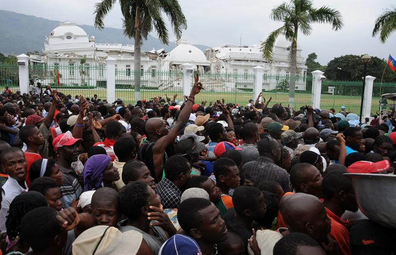 Crowding around a food aid truck in 2010, collapsed Presidential Palace in the background.