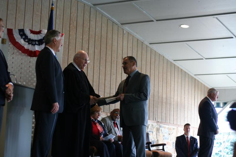 Aziz Aziz shakes hands with U.S. Magistrate Judge James Welsh after receiving his certificate of citizenship. Waiting to congratulate Aziz next is Virginia Governor Terry McAuliffe, who spoke at the ceremony.