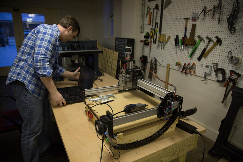 Dan Funk hooks up a computer to the Shapeoko 2, an open source CNC Router, in the Staunton Makerspace warehouse.