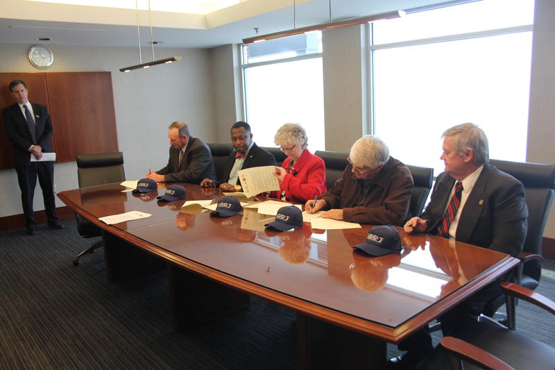 Signing agreement: (Seated l-r) Michael Shull (Augusta County Board of Supervisors), Christopher B. Jones (Harrisonburg City Council), Carolyn Dull (Staunton City Council), Frank Lucente (Waynesboro City Council) and Michael Breeden (Rockingham County)