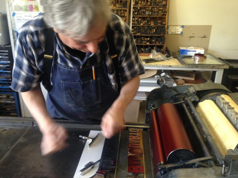 Garret Queen works on one of the center's letterpress machines.