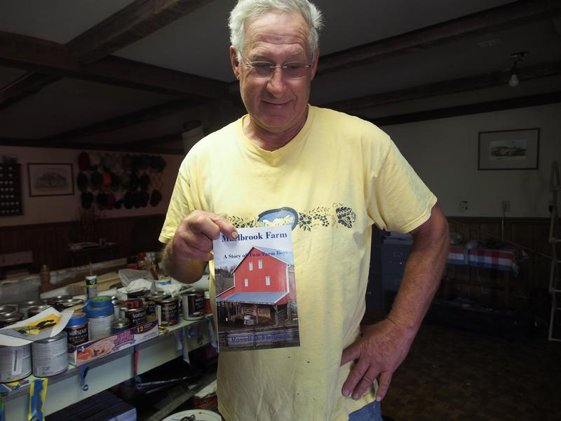 Barn quilter Russell Fleshman holds up a copy of his memoir about growing up in Rockbridge County. It's just one of many hobbies he tackled while in retirement.