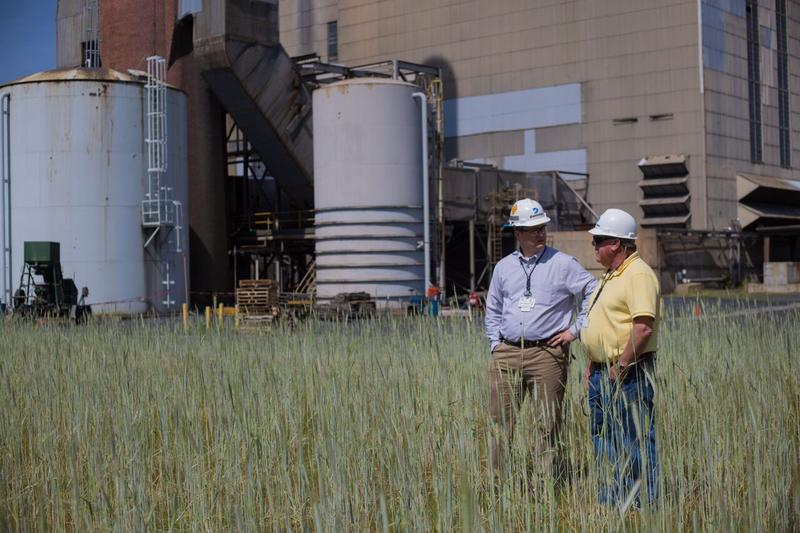 Greg Searcy (on left), the Operations Manager at the Bremo Power station, talks to Dominion Media Relations representative Dan Genest (at right) in front of the station's old coal stacks.