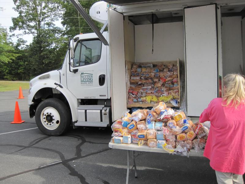 A volunteer unloads loaves of bread off the truck at the Palmyra Mobile Food Pantry.