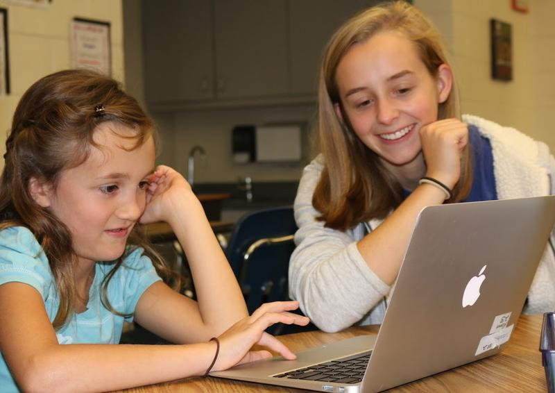 Mentor Megan Bird helps a 7-year old participant learn to code in a program called Scratch. Megan is in 11th grade and says she loves the creativity and patience that the STEM fields require.