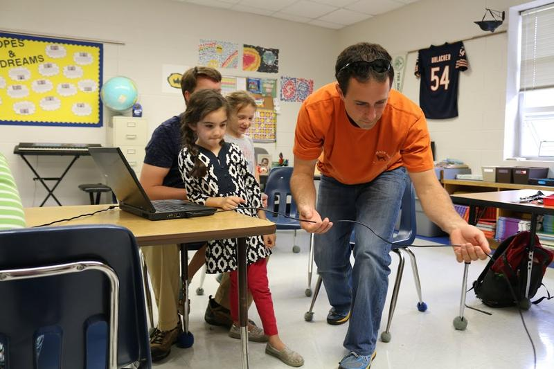 "Justin Callahan untangles the cord connecting his daughter's laptop to her robot during the NXT robotics workshop. He and 6-year old daughter Kinley have attended 3 Girls' Geek Day events. ""It's a fun way to spend some time with your daughter,"" he says."