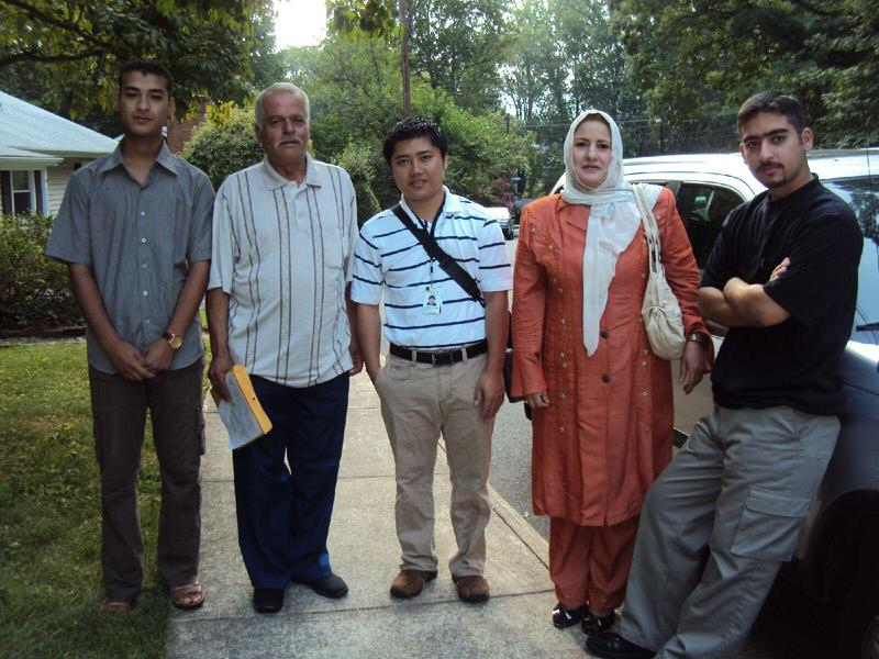 Awadh Alsyra poses with his wife, two of his four sons, and a staff member from the International Rescue Committee on their second day in the U.S.