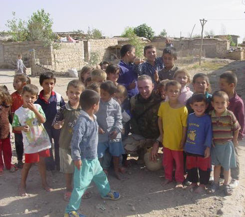 Retired U.S. Army Lt. Col. Tim Leroux pictured with a group of kids in Northern Iraq.