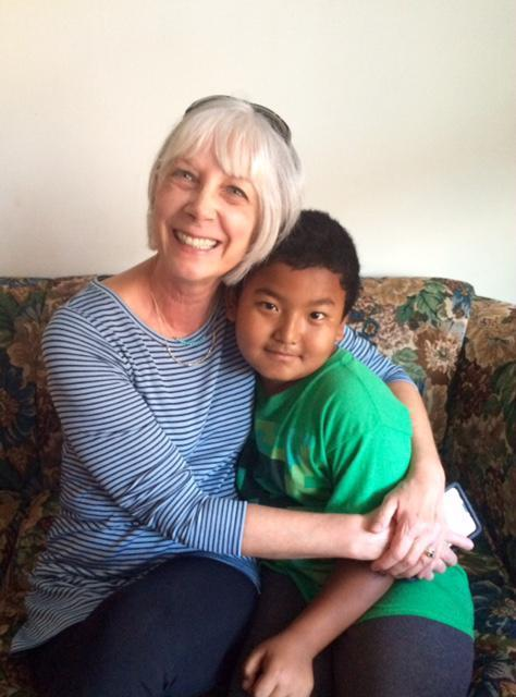 Mary Plank, a volunteer with the International Neighbors non-profit group and a former public school teacher, sits with Bebak, an 8-year old Bhutanese boy whom she helps with school lessons.