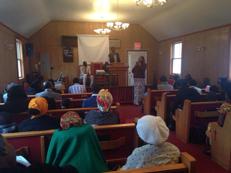 A woman, speaking in Swahili, tells the congregation at the African Lighthouse Baptist Temple about a recent pain in her neck and subsequent surgery at UVA hospital. She says it was nothing compared to what she's already been through.