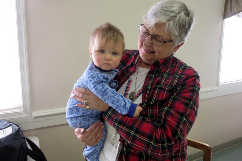 Mary Sue McDonald, chief of Edom Precinct District 2 holds Elijah Scott Frazier while her neighbor votes on Tuesday morning.