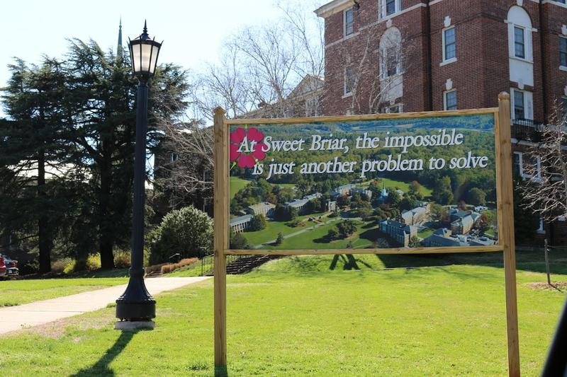 A billboard on campus features an aerial photograph of the 115-year old school.