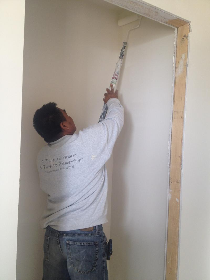 "Win Than, 42, helps paint a closet in his future neighbor's house as part of the ""sweat equity"" portion to Habitat's financing plan."