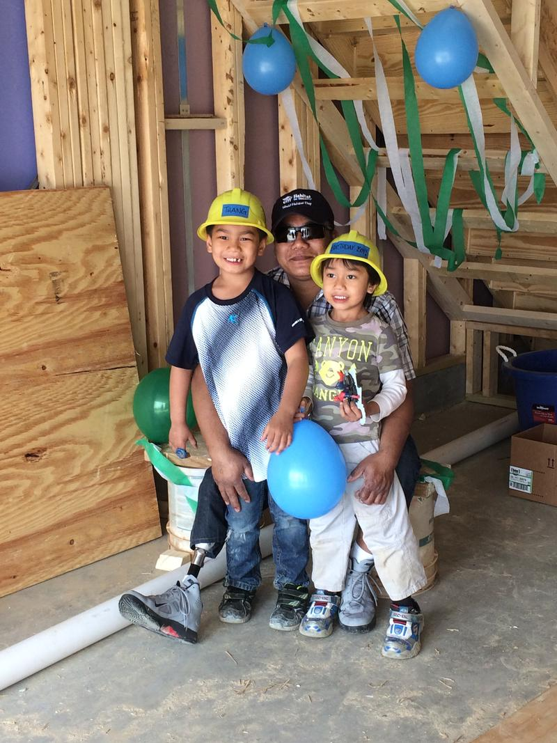 Win Than and his two sons, Thang, 7, and Johnny, 5, who celebrated his birthday on the construction site of their new future house.